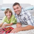 Father and son playing checker game on fur — Stock Photo #68987107