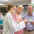 Pharmacist and her customers talking about medication — Stock Photo #68987621