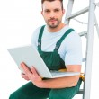 Carpenter sitting on ladder using laptop — Stock Photo #68987767