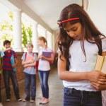 Sad schoolgirl with friends in background at school corridor — Stock Photo #68988055
