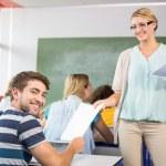Teacher handing paper to student in class — Stock Photo #68988543