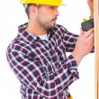 Handyman using measure tape on wooden plank — Stock Photo #68988605