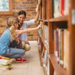 Teacher and little girl selecting book in library — Stock Photo #68989147