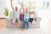 Family with arms raised on sofa — Stock Photo