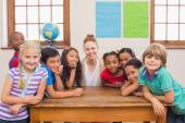 Cute pupils and teacher smiling at camera in classroom — Stock Photo