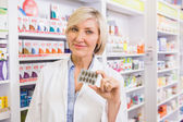 Smiling pharmacist showing blister  — Stock Photo