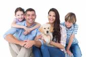 Happy family with cute dog over white background — Stock Photo