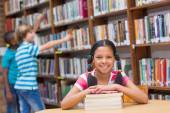 Cute pupils looking for books in library  — Stock Photo