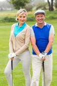 Golfing couple smiling on putting green — Stock Photo