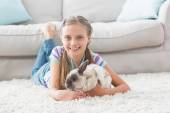 Girl with rabbit lying on rug in room — Stock Photo