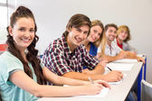 Students writing notes in classroom — Stock Photo