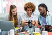 Business people looking at digital camera — Stock Photo