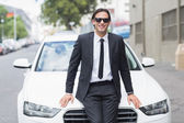 Businessman leaning on the bonnet — Stock Photo