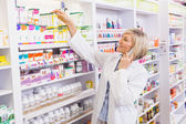 Smiling pharmacist phoning and taking medicine from shelf — Stock Photo