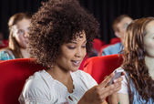 Woman text messaging on her mobile during movie — Stock Photo