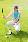 Female golfer kneeing on the putting green — Stock Photo