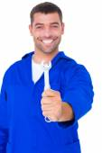 Smiling male mechanic showing spanner — Stock Photo