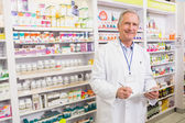 Smiling senior pharmacist writing on clipboard — Stockfoto