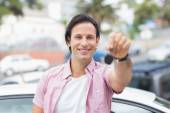 Young man smiling and holding key — Stockfoto