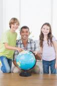 Father with son and daughter exploring map on globe — Stock Photo