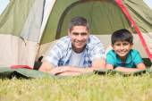 Father and son lying beside their tent — Stock Photo