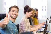 Student gesturing thumbs up in computer class — Stock Photo