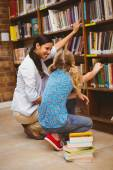 Teacher and little girl selecting book in library — Stockfoto