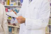 Mid section of pharmacist writing a prescription — Stock Photo