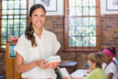 Pretty teacher smiling at camera in library  — Stock Photo