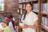 Pretty teacher helping pupil in classroom — Stock Photo