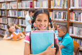 Cute pupil smiling at camera in library — Stock Photo