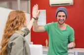 Casual businessman and woman high fiving — Stock Photo