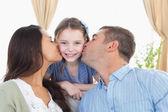 Happy girl being kissed by parents — Zdjęcie stockowe