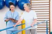 Senior woman walking with parallel bars with therapist — Stock Photo