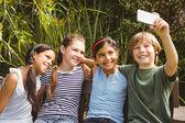 Happy children taking selfie at park — Stock Photo