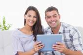 Happy couple holding digital tablet at home — Stockfoto