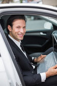 Businessman working in drivers seat — Stock fotografie