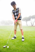 Concentrating golfer lining up his shot — Stock Photo