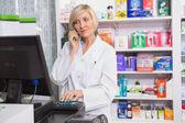 Blonde pharmacist using computer while phoning — Stock Photo