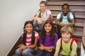Children sitting on stairs in school — Foto de Stock