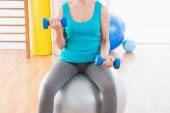 Woman exercising with dumbbells on fitness ball  — Stock Photo