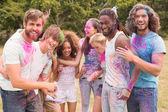 Happy friends throwing powder paint — Stockfoto