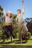 Happy couple jumping in the park — Stock Photo