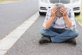 Stressed man sitting on the ground — Stock Photo
