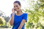 Woman using phone in park — Foto de Stock