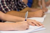 Mid section of students writing notes in classroom — Stock Photo