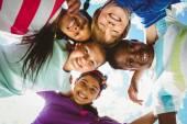Portrait of happy children forming huddle — Stock Photo