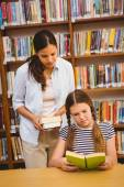 Teacher and girl reading book in library — Foto de Stock