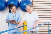 Therapist looking senior woman walking with parallel bars — Stock Photo