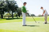 Golfer holding hole flag for friend putting ball — Foto de Stock